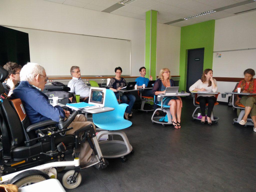 Les participants sont assis et écoutent la coordinatrice.
